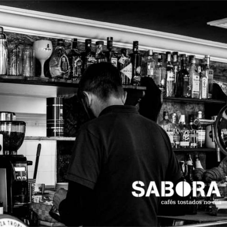 Barra de cafetería galega  con  barista traballando  en máquina de expreso.