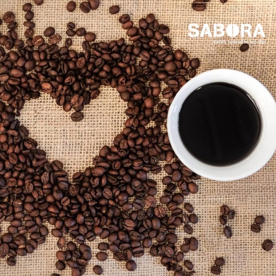 Taza de café y corazón  de granos de café sobre una mesa.