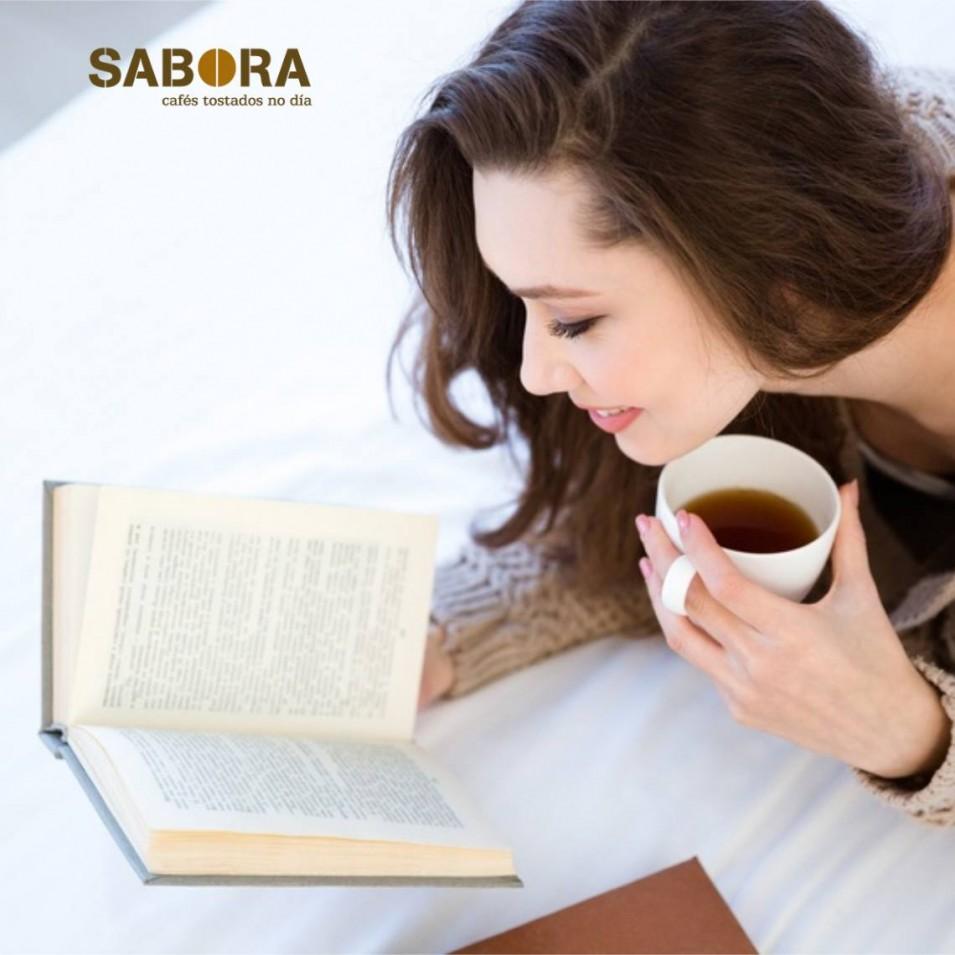 Rapaza lendo un libro cun gran café na casa