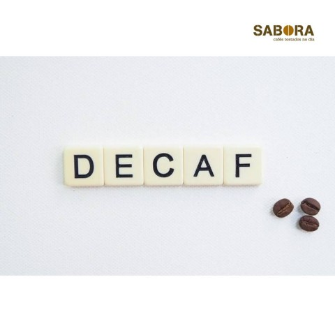 Palabra decaf con tres granos de café